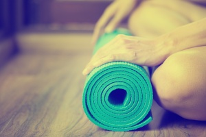 Young woman holding a yoga mat